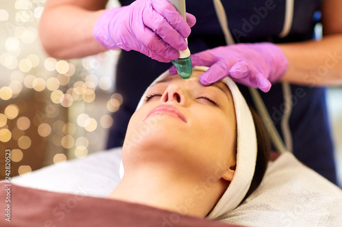 Leinwanddruck Bild people, beauty, cosmetology, exfoliation and technology concept - beautiful young woman having microdermabrasion facial treatment with crystals in spa