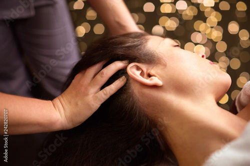Leinwanddruck Bild people, beauty, lifestyle and relaxation concept - beautiful young woman lying with closed eyes and having head massage at spa