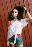 80s retro looking girl touching her curly hair. Summer pop fashion look. - 242821124