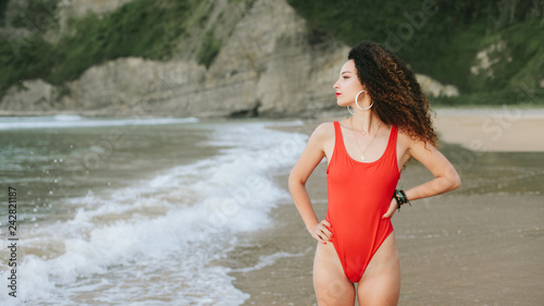 Pretty retro pop style curly hair woman in red swimsuit standing at the beach looking to the sea.