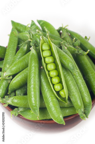 green peas in pods.  in a clay plate on a white background