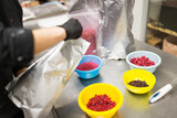 production, cooking and people concept - cook pouring berries into bowl at confectionery shop kitchen