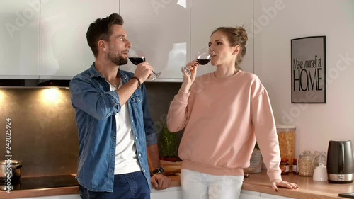 Happy couple drinking red wine in the kitchen