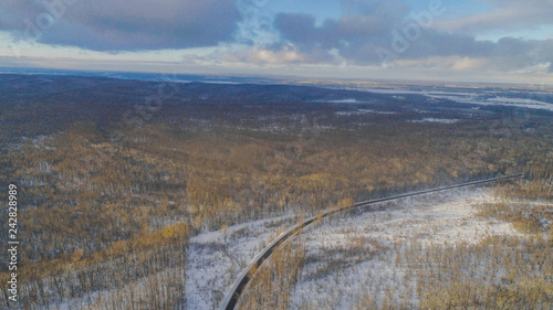 Aiereal wives of the road in winter forest with lot of trees and snow , drone shoot ,Ukraine  - 242828989