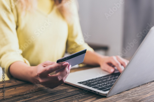 cropped view of woman holding credit card near laptop at home - 242849518