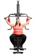 Leinwanddruck Bild - Overweight woman exercising on a fitness machine