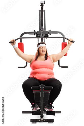 Leinwanddruck Bild Overweight woman exercising on a fitness machine