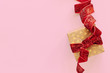 Gift box with red ribbon on pink background. Holiday present card