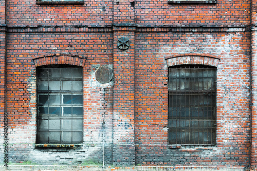 Żyrardów, Poland. Window with iron frame and red bricks wall of old factory. - 242882568