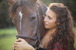 Close up of a pretty girl strocking her horse