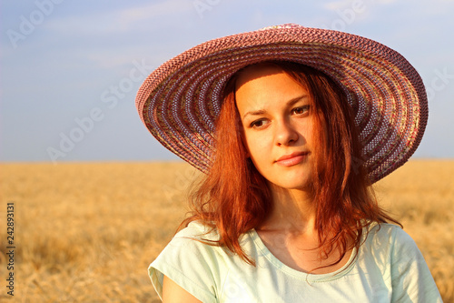 Girl in a hat on yellow wheat field in summer