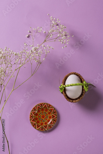 White egg in withe basket with wooden plate on purple background