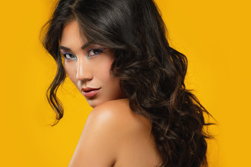 Asian woman with a beautiful curly hair and make-up on yellow background © blackday