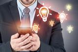 Businessman with smartphone, lightbulbs - 242911542