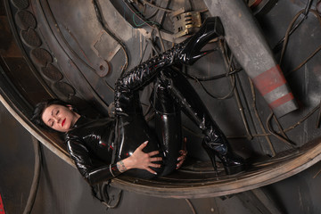 sexy evil mistress posing in black tight latex catsuit
