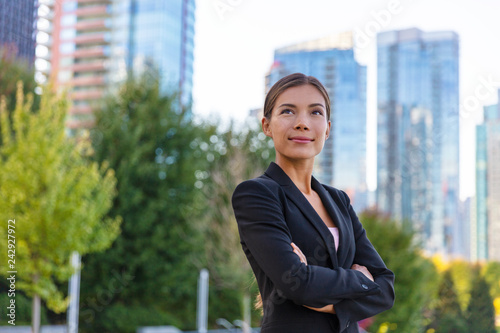 Asian businesswoman. Happy business woman portrait pensive looking up contemplative of her career. City job employment. Chinese professional in black suit confident with crossed arms.