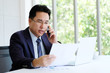 Asian businessman reading papers talking phone and working with laptop computer at office, business concept