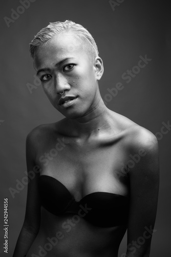 Young beautiful rebellious woman with short hair against gray ba