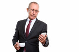 Studio shot of senior businessman holding coffee cup while using