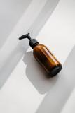 One pump dispenser glass brown bottle for cosmetics, overhead. Direct light. Beauty blogging, salon treatment, minimalism concept - 242955593