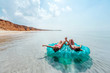 Friends relaxing on inflatable ring on the beach