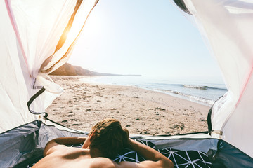 Young travellet inside camping tent on the beach