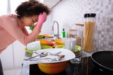 Tired Woman Leaning Near Sink With Dirty Utensils - 242968749