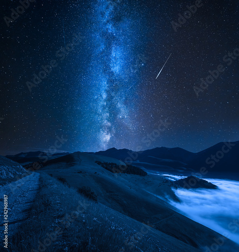 Milky way over foggy valley in the Castelluccio, Umbria, Italy