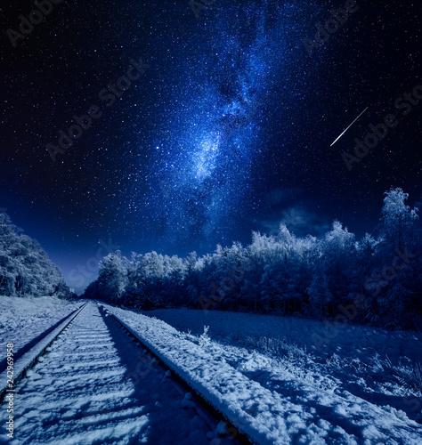Milky way over frozen railway line in winter at night