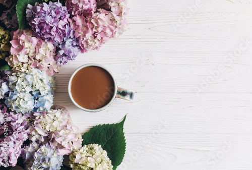 Beautiful hydrangea flowers and coffee cup on rustic white wood, flat lay. Colorful pink, blue, green hydrangea border, greeting card with space for text. Hello spring. Happy mothers day