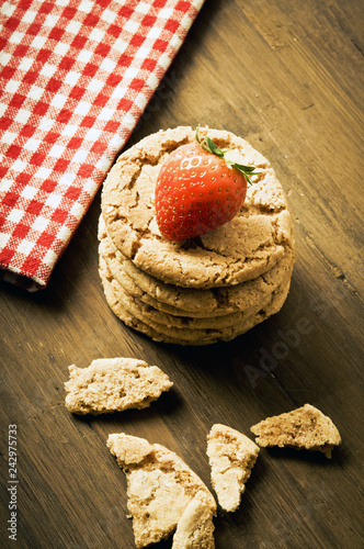 Foto Murales pile of home made cereal biscuits cookies with strawberry up over wood table in rustic style