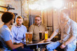 Group of man sitting in a bar with glasses full of beer in front of them. Sitting and having fun.