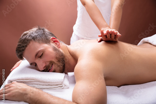 Therapist Giving Back Massage To Man
