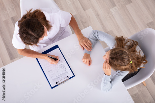 Doctor Sitting With Girl Patient In Clinic