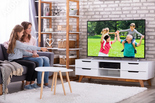 Mother And Daughter Watching Television In Living Room