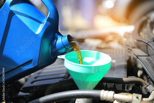 mata magnetyczna Close up of Pouring fresh oil to car engine in auto repair service, Change oil