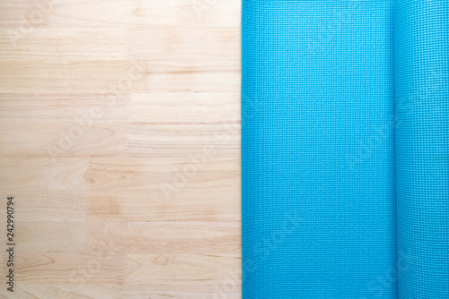 close up of blue yoga mat on the table, sport and healthy concept