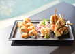 Sushi on black plate on black table with sea view from restaurant  - 242991589
