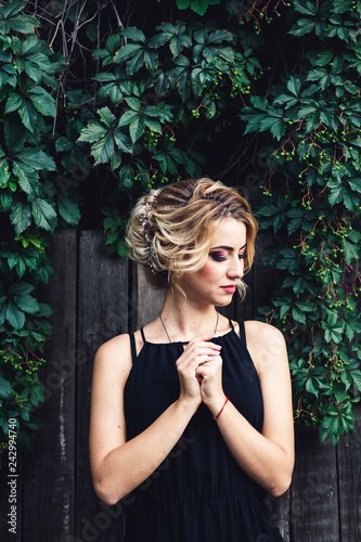 Elegant model shows her gorgeous hairstyle with hair decor. Beautiful girl posing against the backdrop of a dark green wild vineyard.