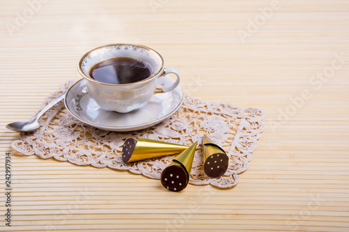 Foto Murales A Cup of hot coffee with delicious sweets on a light background
