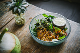 Vegan salad with various veggies and greens, and dressing in a glass bowl on a wooden table. Closeup, food blog, healthy eatingrecipe - 243005544