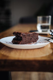 One slice of vegan chocolate brownie cake on wooden table. Sugar free, wheat free, dairy free, flourless dessert. Dark mood food photo. Healthy eating, lifestyle concept. Copy space - 243006356