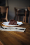 One slice of vegan chocolate brownie cake on wooden table. Sugar free, wheat free, dairy free, flourless dessert. Dark mood food photo. Healthy eating, lifestyle concept. Copy space - 243006779
