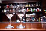 Two clean empty glasses on a blurred background of the bar. - 243018917