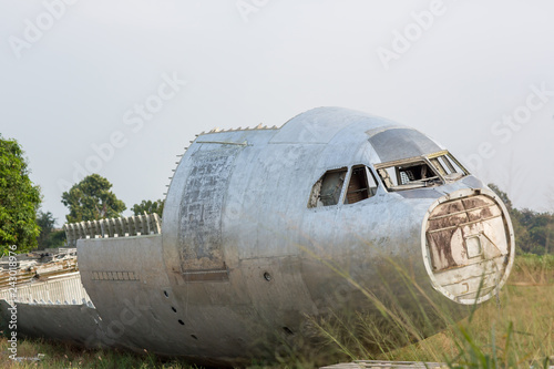 obraz PCV crash-landed aircraft. airplane wreckage in jungle - old propeller aircraft in forest. an airplane tail in a plane crash site. Exterior of an old abandoned and rusted airplane fuselage.