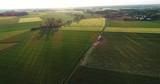 Tiefstehende Sonne über Feldern aus der Luft - 243024347