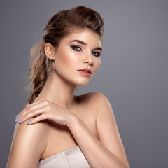 Beautiful face of young caucasian woman with perfect health skin - over grey background. Skin care concept. Female Model touches body. © Valua Vitaly