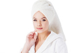 Beauty treatments after the bath. Portrait of a young beautiful woman in a Terry robe and with a towel on her head. - 243025189