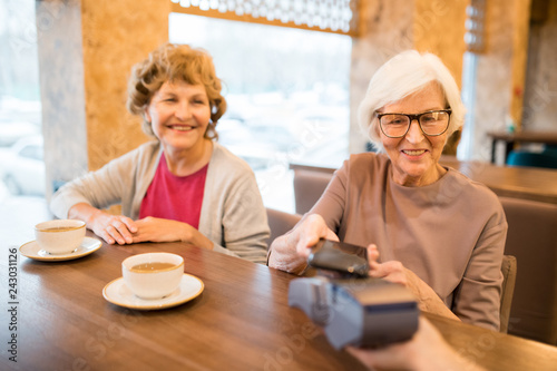 Foto Murales Cheerful modern senior ladies paying for tea with smartphone: smiling gray-haired lady sitting at table and putting gadget to payment terminal