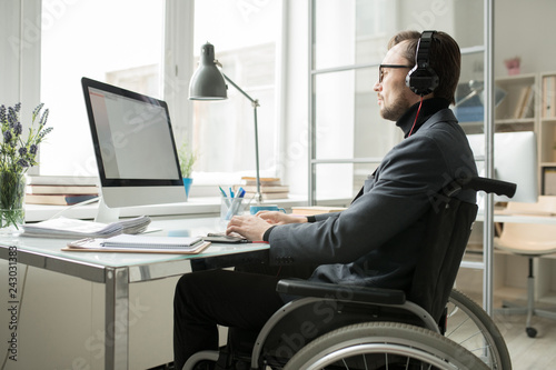 Disabled businessman in wheelchair wearing headphones and concentrated on his work, he typing on keyboard and looking at computer screen